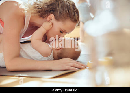 Mother kissing her baby while working out on a yoga mat - Stock Photo