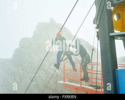 Germany, Bavaria, Garmisch-Partenkirchen, Zugspitze, installers working on steel rope of a goods cable lift - Stock Photo