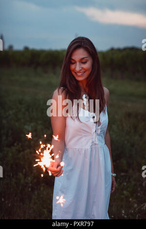 Young woman in nature, burning sparkler in the evening - Stock Photo