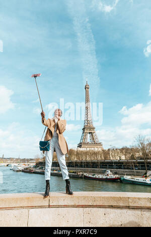 France, Paris, Woman standing on bridge over the river Seine with the Eiffel tower in the background taking a selfie - Stock Photo