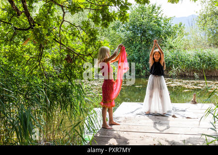 Two girls standing on jetty at a pond in fancy dresses - Stock Photo
