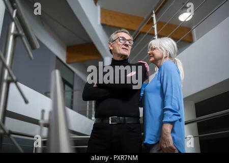 Senior woman supporting senior businessman on office stairs - Stock Photo