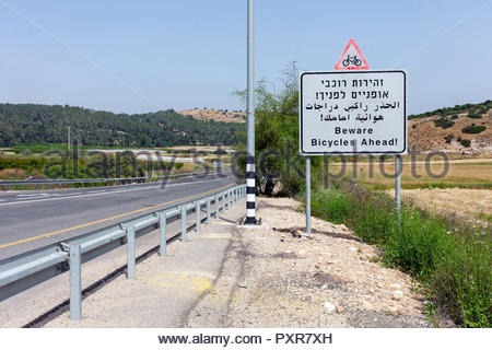 'Beware Bicycles Ahead' road sign written in Hebrew, Arabic, and English on an Israel highway - Stock Photo