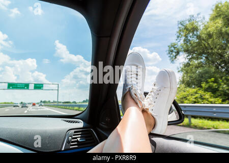 Italy, feet of woman leaning out of car window - Stock Photo