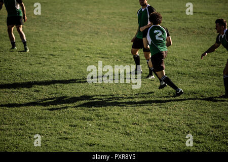 Men playing a game of rugby on a sports field. Rugby players in action on pitch during the match. - Stock Photo