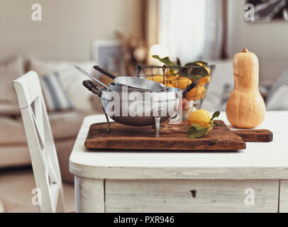 Nostalgic kitchen utensils and fruits on old wooden table - Stock Photo