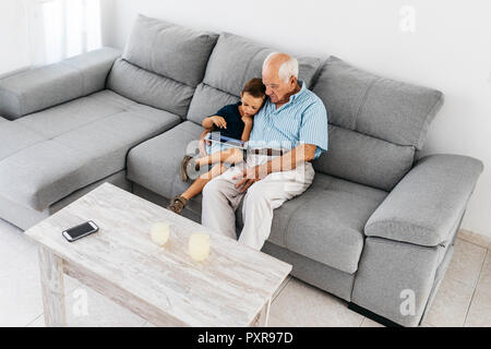 Grandfather and grandson sitting together on the couch at home looking at digital tablet - Stock Photo