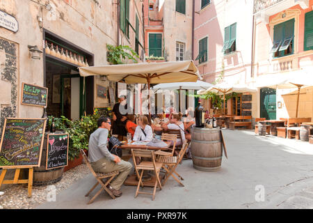 People relaxing at a sidewalk trattoria in Monterosso al Mare, a town and comune in the province of La Spezia, part of the region of Liguria. It is on