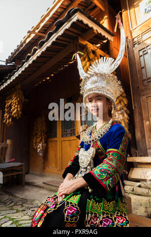 China, Guizhou, portrait of a young Miao woman wearing traditional dress and headdress - Stock Photo