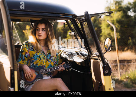 Young woman sitting in a van playing guitar - Stock Photo