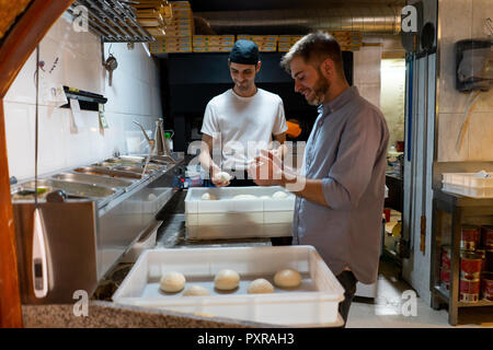 Two men with raw dough in boxes in kitchen of a pizzeria - Stock Photo