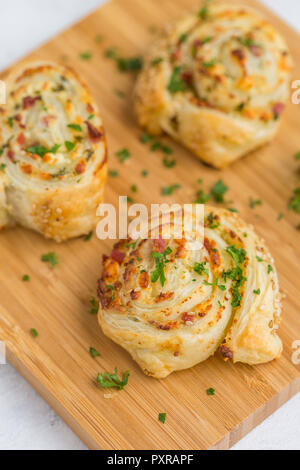 Sticky buns with feta, cream cheese, bacon and parsley on wooden board - Stock Photo