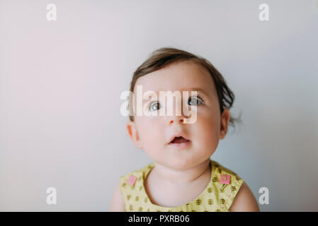 Surprised baby girl looking up on white background - Stock Photo