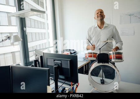 Businessman making noise with drums in his office - Stock Photo