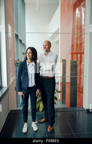 Portrait of a successful business team, standing in office builging - Stock Photo