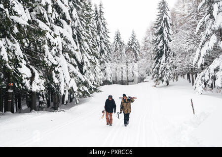 Italy, Modena, Cimone, couple with skiers and snowboard walking in winter forest - Stock Photo