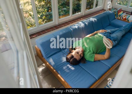 Mature woman lying on couch at home reading book - Stock Photo