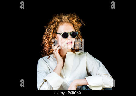 Portrait of stylish young woman with curly red hair wearing sunglasses in front of black background - Stock Photo