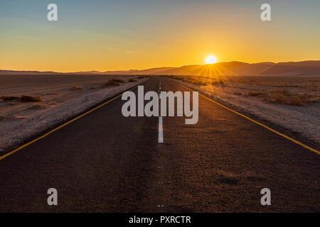 Africa, Namibia, Namib desert, Naukluft National Park, empty road at sunset - Stock Photo