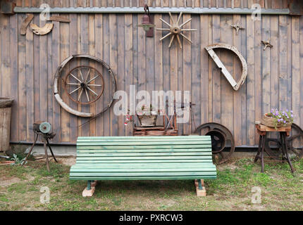 Recreation area near a simple village house outdoor concept. Wooden green bench and  flowers in baskets on grass lawn. Cloudy autumn day rural landsca - Stock Photo