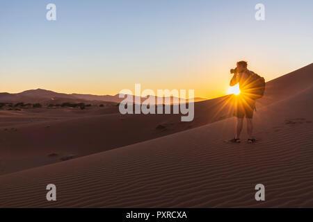 Africa, Namibia, Namib desert, Naukluft National Park, photographer on dune during sunrise - Stock Photo