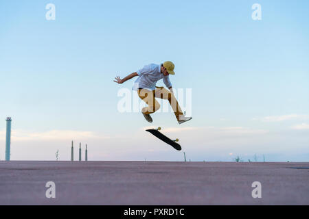Young man doing a skateboard trick on a lane at dusk - Stock Photo
