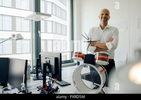 Businessman standing in his office, plaing drums - Stock Photo