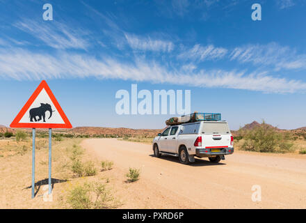 Namibia, Erongo Region, off-road vehicle on sand track, deer crossing sign with elephant - Stock Photo