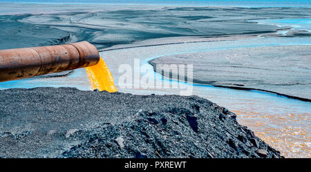 The industrial wastewater is discharged from the pipe into the water. - Stock Photo
