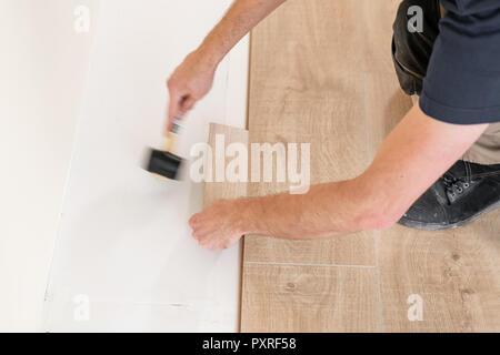 Installing laminate flooring fitting the next piece - focus on hand. Man laying laminate flooring - Stock Photo