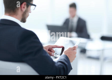 close-up businessman concentrated watching in touch pad while si - Stock Photo