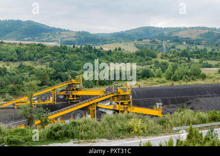 Huge industrial machine for coal mining in hilly landscape - Stock Photo