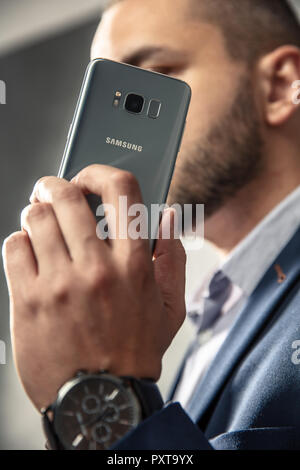 WROCLAW, POLAND -  OCTOBER 17th, 2018: An elegant man in suit holds his smartphone. Samsung Galaxy S8 is android phablet smartphone produced by Samsun - Stock Photo
