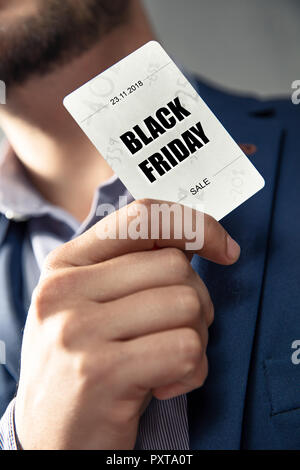 Black Friday's Sale card holded by an elegant man in suit. Conception of Black Friday's sales and discounts at shops.