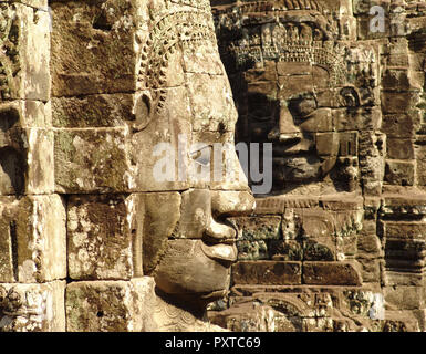 Bayon Temple at Angkor, in Siem Reap,  Cambodia, showing two of the smiling faces of Buddha, carved in the 12th century. - Stock Photo