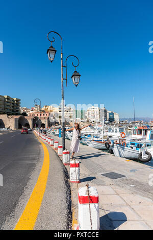Elegant young tourist visitor woman walking on a sightseeing tour at Heraklion Venetian port, Crete, Greece  - Stock Photo