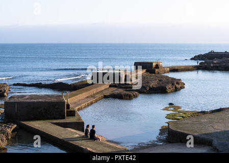 Estoril, Portugal - July 9, 2018: Young couple sitting on concrete steps of sea water pool next to sea by boardwalk in Estoril Portugal - Stock Photo