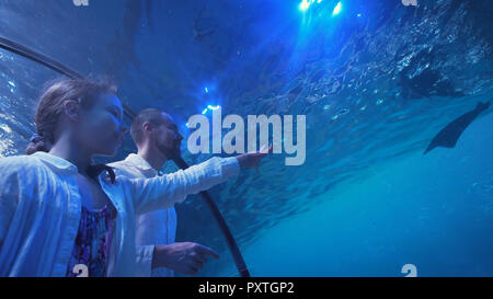 Teenage girl with Dad amusingly watching the fish in Aquarium - Stock Photo