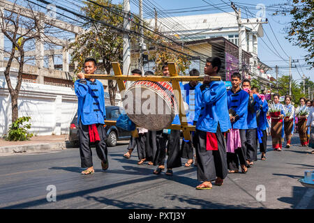 Young men in blue outfits carry drums and march down the street in Chiang Mai. - Stock Photo