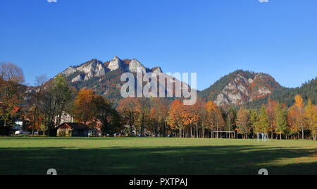 Panoramic view at Three Crowns massif in Pieniny Mountains, Poland, from valley, Small village, trees in autumnal (fall) colors. - Stock Photo