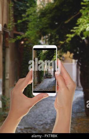 A tourist is taking a photo of one of the streets in the Trastevere area in Rome, Italy on a mobile phone - Stock Photo