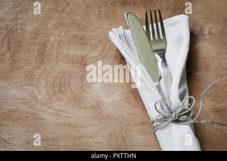 Fork and Knife Tied on White Napkin on wooden table. Table setting. Top view. Selective Focus. Rustic Style. - Stock Photo