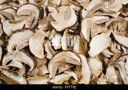 Dried porcini mushrooms in a wooden plate on a wooden table. Food background. Rustic Style. Selective focus. - Stock Photo