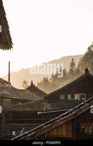 China, Guizhou, houses of a Miao settlement in backlight - Stock Photo
