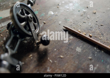 Close-up of old hand drill and pencil in workshop Stock Photo