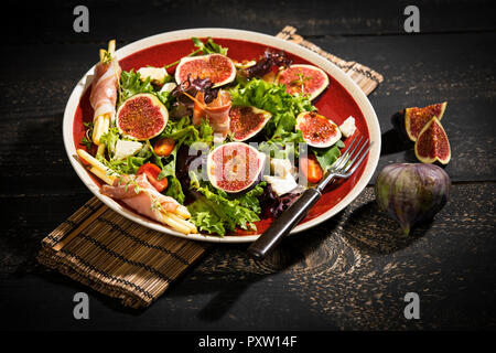 Mixed salad with figs, tomatoes, sheep cheese, grissini with ham on plate - Stock Photo