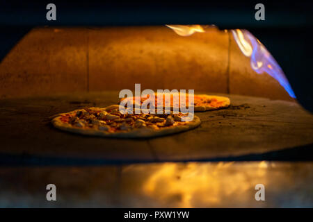 Two pizzas in oven - Stock Photo