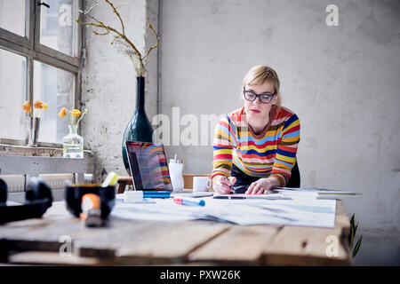 Portrait of woman working at desk in a loft - Stock Photo