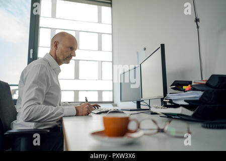 Businessman working on his computer, taking notes
