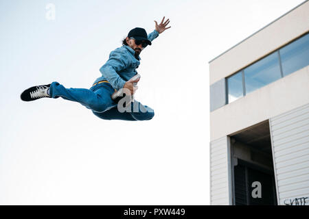 Trendy man in denim and cap doing jump - Stock Photo